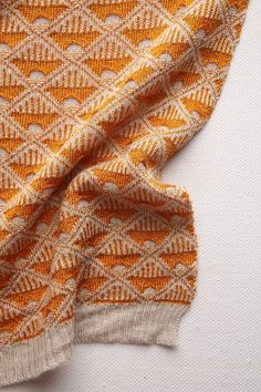 "I would love to try to reproduce this fabric. I love the little ""peek-a-boo"" holes that allow the reverse stockinette to show through from the back. And . . . orange!"