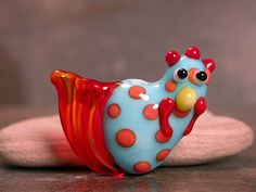 It's a chicken or technically a rooster? Whichever, it's glass and a bead!