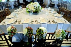 table setting and flowers for bride and groom chairs