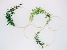 Varied sizes of gold metal hoops accented with Italian ruscus, spirea, white Polo roses, and ivory spray roses