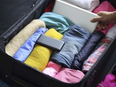 Rolled clothing packed in suitcase. - lzf/Getty Images