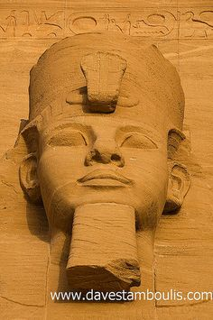 closeup of the pharaoh Ramses at the sun temple of Abu Simbel lit up in early morning sunlight in Upper Egypt