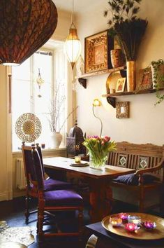 Bold colored velvet cushions, antique furniture, ethnic lighting, peacock feathers, flowers - everything about this dining are is bohemian. I love it!