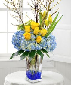 SPRINGTIME SPLENDOR Spread the joy of springtime with this beautiful arrangement filled of blue hydrangea, yellow roses and yellow tulips.