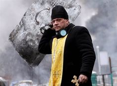 A priest holds a cross and shield during clashes between anti-government protesters and riot police in central Kiev on Feb. 20. Ukraine was the scene of fierce clashes between baton-wielding protesters demanding the ouster of President Viktor Yanukovych and riot police. (Sergey Gapon / AFP - Getty Images)