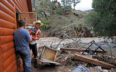 Chris Rodes helps Fred Rob salvage a friend's belongings after floods left homes and infrastructure in a shambles, in Lyons, Colorado