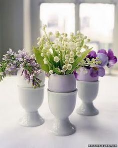 Lilacs, lilies of the valley and pansies in egg shells nested in porcelain egg cups