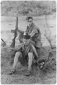 US Soldier guards an NVA soldier he captured during a ground movement ten miles northeast of An Hoa., 1968