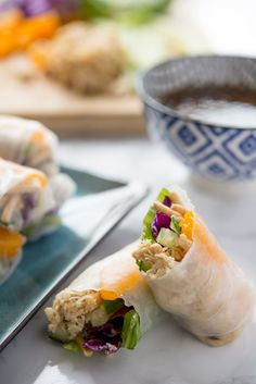 Spring rolls are one of my favorite foods, and spring rolls with peanut sauce are even better! They've got just the perfect blend of vegetables, noodles, and protein, all wrapped up together in soft, chewy rice paper rolls. Plus, they come with a dipping sauce! EASY spring recipe for lunch or dinner. You'll need soy sauce, ginger, cucumber, rice paper wrappers, Mandarin oranges, shredded chicken, chow mein noodles, romain lettuce, and red cabbage.