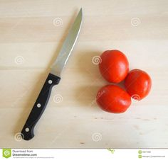 A knife and some tomatoes on a desk