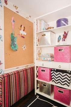 Chevron and metallic storage bins are perfect for stowing games, books and art supplies while keeping the bookshelf orderly in this neutral eclectic girl's playroom. Meanwhile, a large bulletin board proudly displays invitations and keepsakes.