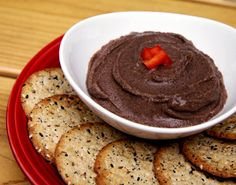 Spicy Black Bean Hummus 1 peeled clove garlic 1 small jalapeño pepper, chopped (or 1/2 teaspoon cayenne pepper) 15-ounce can Eden black beans, rinsed and drained  1 tablespoon tahini Juice from one lemon 2 tablespoons olive oil Salt and pepper to taste  Add garlic and jalapeño pepper to a food processor or blender and puree. Add in remaining, mix til smooth. Store in fridge up to a week.