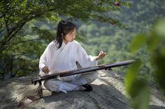 Master Xuanzhen is performing Guqin in the Wulong River scenic spot. wudangmartialarts.com