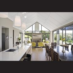 With so much natural light pouring into the family room pavilion, the upper windows have been double glazed to limit heat transferral at this level. The kitchen is designed for entertaining, with a rear space used for cooking and the island for serving. Warm wood floors run right through the home's public spaces, providing material continuity and a sense of progression to the design.