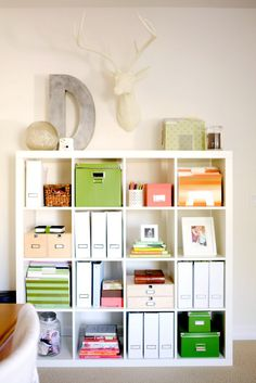 This bookshelf is organized without looking cluttered. By using a unified color scheme and leaving plenty of space for personalization, this shelf is both practical and pretty.