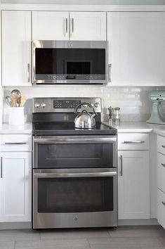White shaker Lowe's Arcadia Cabinets frame a GE stainless steel microwave mounted above a GE oven range positioned on Style Selections Leonia Silver Porcelain Floor Tiles and flanked by cabinets finished with white quartz countertops lined with American Olean Starting Line Gloss White Ceramic Wall Tiles.