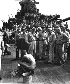 Communal activity: Japanese POW is washing himself under the stare of dozens of crew members of USS New Jersey as soon as he and other Japanese POWs have been transferred aboard ship. The wash will be followed by delousing and the issue of navy fatigues.The whole scene is rather weird. December, 1944.
