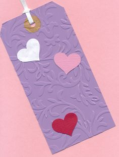Ran a heavy tag through Cuttlebug with one of their embossing folders, added hearts with a Fiskars punch