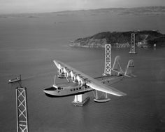 The Sikorsky S-42 Pan American Clipper flying past the unfinished San Francisco Oakland Bay Bridge on its way to Honolulu on April 16, 1935 with Captain Edwin C. Musick in command.    This was the first commercial flight to Hawaii and helped pave the way for the upcoming flights of the Martin M-130 and the China Clipper.