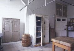 the white wood cupboard, an early refrigerator, offered food storage on one side with hatch doors for blocks of ice from the underground ice house on the other.