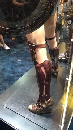 Museum display of Gal Gadot's screen costume - with authentic battle damage! - ref: legplates and sandal covers.