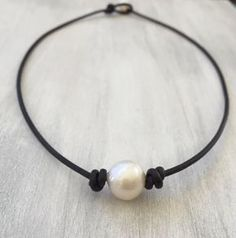Simple yet elegant leather pearl choker. This pearl leather necklace is made with a beautiful 12 - 13 mm high luster freshwater pearl on a 2 mm genuine leather cord. For the clasp I used a 8 mm button freshwater pearl. Check out my other listings for a matching bracelet!  I hand pick all my pearls to ensure you get the best quality.  Color: dark brown  Length of necklace shown: 16 inches  Available in different lengths and color. Please select your desired length and color from the scroll…
