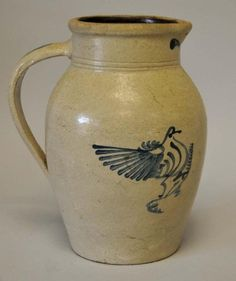 Cobalt Decorated Stoneware Pitcher 	      	                 Salt-glazed, elongated ovoid form with two incised  rings, brushed cobalt bird on branch decoration;  additional cobalt on reverse side, flanking spout,  and on handle; Albany slip interior glaze; 12H