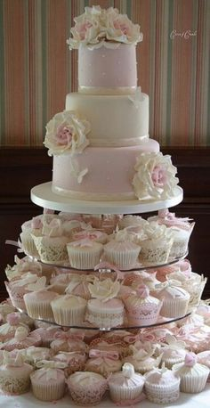 Wedding cake for the couple up top and cupcakes for the guests below!