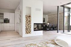 Wohnzimmer, Rückzugsort mit Kamin und der Inszenierung von Brennholz als Deko-Element. Das Glaselement lässt Sommer und Winter viel Licht in die Räume.