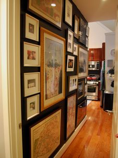 Gallery Wall - wall painted black, classic and simple framing and matting style.  Great idea for a hallway!