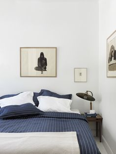 minimal bed with mid-century modern task lamp on night stand. navy bedding
