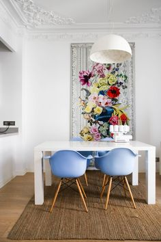 Floral art, blue mcm chairs, white parsons table - very chic, colorful dining room inspiration // pops of color against white walls
