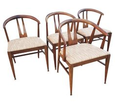 """Set of Four Mid-Century Modern Walnut """"Wishbone"""" Dining Chairs, in the Style of Hans Wegner. One """"Captain's"""" chair and three guest chairs. Excellent condition with age wear and patina, shown in photos. New upholstery.Seat height 19.5""""  The seller offers very economical curbside delivery to New York City, Philadelphia and anywhere within 90 miles of zip code 18018. Please contact support@chairish.com for more details."""