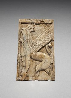 Ivory furniture decoration from Nimrud carved in low relief with a rearing winged griffin facing left. One paw rests on a papyrus or lotus head, the other raised. 8th – 7th century BC. Phoenician style