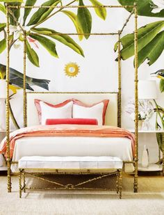 Tropical inspired bedroom with printed wallpaper, a bamboo canopy bed, and a bamboo ottoman
