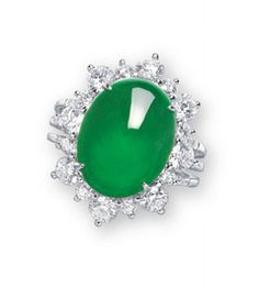A JADEITE AND DIAMOND RING   Set with an oval jadeite cabochon of vivid emerald green colour and very good translucency, within a brilliant-cut diamond surround, to the diamond-set quarter-hoop, mounted in 18k white gold, cabochon approximately 15.0 x 11.5 x 6.4 mm, ring size 6. Price realized: 325K HKD (USD 42,065)