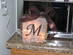 These make great gifts! Just purchase a glass block from craft store, fill with lights, print design and monogram or saying on transparent scrapbook paper and wrap with ribbon!