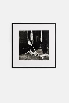 One of the most influential photographers of the 20th century, Helmut Newton (1920–2004) was a tireless explorer of the connections between voyeurism and sensuality. In this 1989 image, a nude woman sprawls on a mansion floor, extending her arm to a man with a video camera. She gestures toward him as the camera glides over her body. The videographer watches the woman, as we, the viewer, look over them both—undetected.