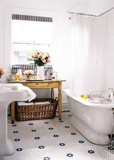 Nice bright bathroom with a great tub.  Love the wood table and basket for storing towels. Love the floral tile floor.