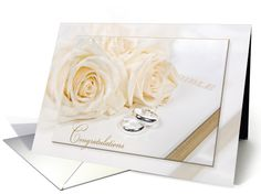 Wedding-white roses with rings on white Holy Bible card