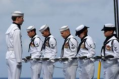Sailors assigned to the honor guard aboard the Nimitz-class aircraft carrier USS Ronald Reagan (CVN 76) bow their heads during prayer at a burial-at-sea ceremony.