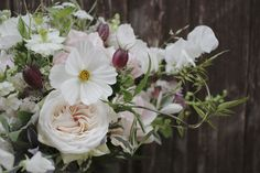 Natural wild and whimsical bridal bouquet created from a mix of British Garden Flowers, Garden O'hara Roses, Seed Pods and Vine. Whites, blush pinks, greens