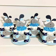 Set of 4 baby whale themed diaper cake centerpieces for your boy baby shower. Color scheme is gray, navy blue, and light blue. Baby whales are on each side.