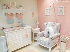 A poltrona de amamentação é azul com flores rosa estampadas harmonia com trocador do bebê que conta com um enxoval rosa e azul.