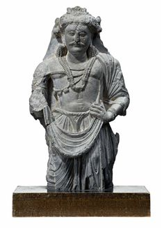 A STANDING BODHISATTVA, GHANDARAN, GREY SCHIST, 3RD CENTURY standing with a slightly bent left leg, clad in princely attire with turban and heavily decorated with jewellery 54cm high