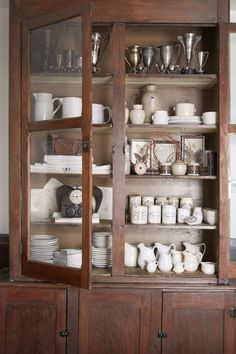 """Assorted trophies, which Lindsea prefers unpolished are on display alongside ironstone pitchers, plates, creamersand jelly jars, old Bibles, framed butterflies, hand-painted apothecary crocks, ram horns, and more. """"I get a little carried away,"""" Lindsea says."""