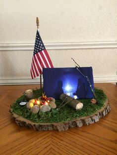 Cub Scout Blue and Gold Lighted Camping Centerpiece. The tent is made out of hard clear plastic with a couple of paper silhouette figures taped to the side of the tent. I covered the tent with blue fabric and placed a cheap $ store book light in the tent. I added a lighted Campfire that I already had made and some misc camping stuff on a sheet of moss on a wood round.