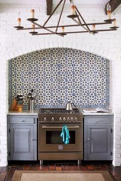 Amazing kitchen features a ceiling accented with rustic wood beams situated over a white brick wall fitted with an arched alcove filled with a stainless steel stove under a blue mosaic tiled backsplash next to an integrated microwave.