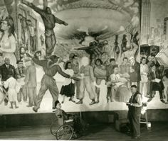Diego Rivera working on mural with Frida Kahlo.