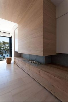 A modern fireplace with timber which rises up and over the kitchen and dining rooms